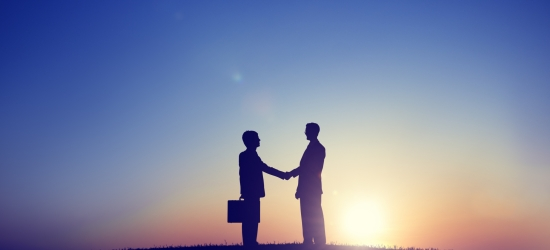 Two Businessmen Shaking Hand in Back Lit